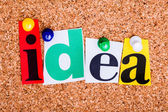 The word idea in cut out magazine letters pinned to a cork notic — Stock Photo