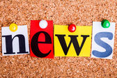 The word news in cut out magazine letters pinned to a cork notic — Stock Photo
