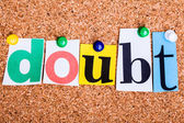 The word doubt in cut out magazine letters pinned to a cork noti — Stock Photo