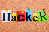 The word Hacker in cut out magazine letters pinned to a cork not — Stock Photo