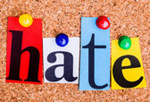 The word hate in cut out magazine letters pinned to a cork notic — Stock Photo