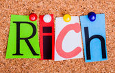 The word Rich in cut out magazine letters pinned to a cork notic — Stock Photo
