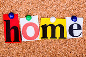 The word Home in cut out magazine letters pinned to a cork notic — Stockfoto