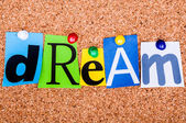 The word Dream in cut out magazine letters pinned to a cork noti — Stock Photo