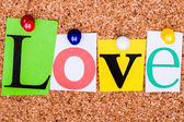 The word Love in cut out magazine letters pinned to a cork notic — Stock Photo