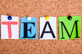 The word TEAM in cut out magazine letters pinned to a cork notic — Stock Photo