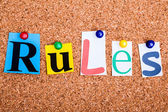 The word Rules in cut out magazine letters pinned to a cork noti — Stock Photo