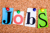 The word Jobs in cut out magazine letters pinned to a cork notic — Stockfoto