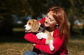 Chica jugando con su perro en el parque otoño — Foto de Stock