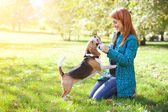 Girl playing with her dog in autumn park — Stock Photo