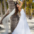 Beautiful caucasian bride posing at a tropical beach — Stock Photo