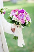 Groom holding a beautiful wedding bouquet — Stock Photo