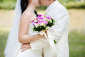 Kissing couple and wedding bouquet — Stock Photo