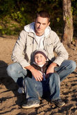 Young father and his little son are sitting and looking at the camera — Stock Photo