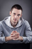 Closeup of young man with hand on head on gray background — Stock Photo