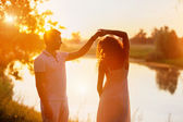 Young beautiful couple in white dancing on the background of sunset — Stock Photo