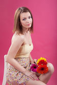 Sweet girl with a bouquet of flowers sitting on a chair on a pink background, studio shot — Stock Photo