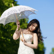Portrait of the bride with decorative umbrella against background green summer park — Stock Photo