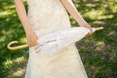 Lace umbrella in hand of the bride — Stock Photo