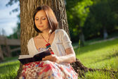 Young woman in the shade of a tree reading a book — Stock Photo