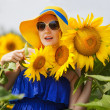 Beautiful young woman in a hat and glasses on a field of sunflowers — Stock Photo