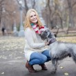 Young beautiful girl with her dog mittelschnauzer in autumn park — Stok fotoğraf