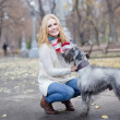 Young beautiful girl with her dog mittelschnauzer in autumn park — Lizenzfreies Foto