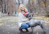 Young beautiful girl with her dog mittelschnauzer in autumn park — Stock Photo
