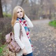 Blonde girl in a sweater with a backpack in autumn park — Stock Photo