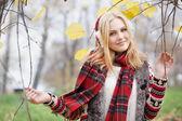 Girl in fur headphones in the autumn park — Stock Photo