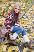 Young blond woman sitting on yellow leaves in the park — Stock fotografie
