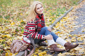 Young blond woman sitting on yellow leaves in the park — Stock Photo