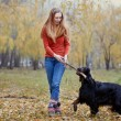 Girl and her dog playing in the autumn park — Stock Photo