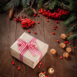 Fir tree  branches, rowan berries, Christmas gift on a wooden background — Photo