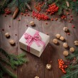 Fir tree  branches, rowan berries, Christmas gift on a wooden background — Stock fotografie