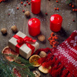 Christmas candles, gifts and fir tree  branches on a wooden background — Stock Photo