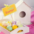 Easter eggs, green grass, wooden birdhouse on a pink tablecloth — Stock Photo