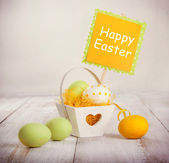 Colorful easter eggs in a decorative basket on wooden background — 图库照片