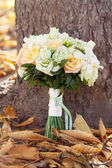 Bridal bouquet and autumn leaves — Stock Photo