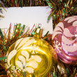 Cristmas card on tinsel background with two baublesvpurple and yellow - Stock Photo