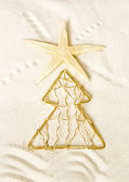 Seastar on a wavy sand background and xmas-tree — Stock Photo
