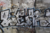 Graffiti on the peeled off plaster wall background — Stock Photo