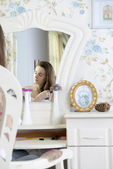 Portrait of a young woman at the mirror — Stockfoto
