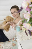 Young woman in the children's room on the bed — Stock Photo