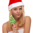 Young blond woman in santa hat with candy — Stock Photo