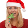 Young blond woman in santa hat with candy — Stock Photo #16970845