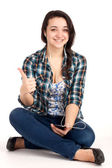 Teenage girl sitting and listen music — Stock Photo