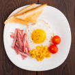Fried egg with toasts, ham and cherry tomato — Stock Photo #28574807