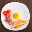 Fried egg with toasts, ham and cherry tomato — Stock Photo #28874695