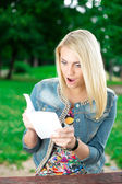 Surprised young woman with book in park — Stock Photo